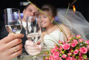 bride and groom drinking champagne in a limousine